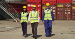 Portrait of dock workers at an industrial harbor walking towards the camera. Stock Footage