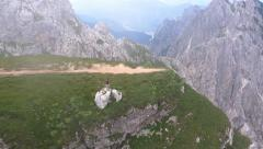Aerial - Mountaineer walking on a long narrow grassy mountain top Stock Footage