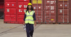 Portrait of a dock worker at an industrial harbor walking towards the camera. - stock footage
