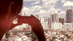 Taking photos of Kuala Lumpur cityscape on mobile phone with light leak effect, - stock footage