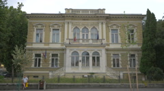 Man sitting in front of Baiulescu House, Brasov Stock Footage