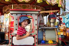 Sweet boy, riding in a train on a merry-go-round, carousel attraction in Euro Kuvituskuvat