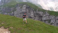 Aerial - Young man hiking in the mountains in spring Stock Footage