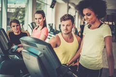 Trainer explaining how to use treadmill Stock Photos