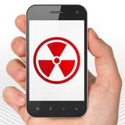 Science concept: Hand Holding Smartphone with Radiation on display - stock illustration