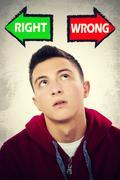 Teenage boy facing choice between RIGHT and WRONG - stock photo