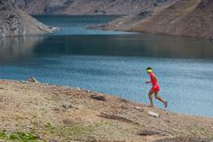 Irl runs alone among alpine lakes Stock Photos