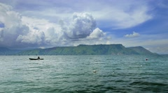 View of Lake Toba with  fisherman on small boat and dynamic clouds. 4K Stock Footage