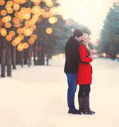 Silhouette of loving couple embracing in warm winter day with lights bokeh, v Stock Photos