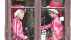 Two children, boys, sitting on a window daytime, waiting for Christmas Stock Footage