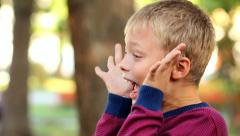 Cheerful kid making funny faces while playing outside on sunny autumn day Stock Footage