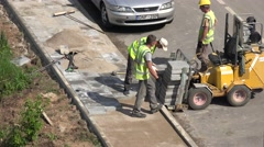 builders group take tiles and lay pave on sidewalk pavement. 4K - stock footage