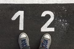 Sneakers on asphalt road with 1 and 2 number - stock photo