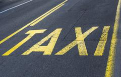 Yellow road sign on asphalt - taxi sign. - stock photo