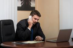 Businessman Talking On Telephone In Office - stock photo