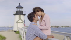 Woman Sits In Front Of Lighthouse, Puts Her Head Against Her Boyfriend's Stock Footage