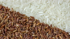 Background of natural brown and white rice seeds, close-up rotation. Stock Footage