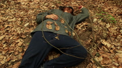 Dead or drunk young woman lying on the ground among the withered leaves-frontal Stock Footage