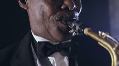 Old african black colored man playing saxophone tuxedo face Stock Footage