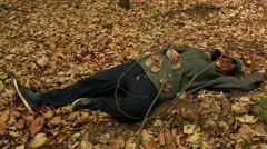 Dead or drunk woman lying on the ground among the withered leaves - stock footage