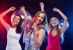 Stock Photo of three smiling women dancing and singing karaoke