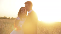 Beautiful young couple bride and groom in a wedding dress at sunset in a wheat Stock Footage