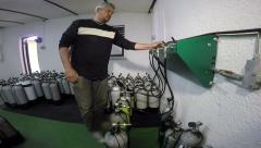 Man Using Diving Air Compressor to Refill Diving Cylinders - stock footage