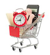 Piggy bank with alarm clock in shopping cart - stock photo