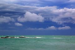 sea stormy landscape over rocky coastline - stock photo