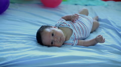 Infant lying on his back and begins to cry. Stock Footage