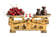 Stock Photo of Cherries on the old fashioned scales with kettlebells. Isolated on white back
