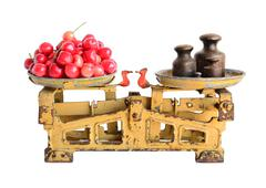 Sweet cherries on the old fashioned scales with kettlebells. Isolated on whit Stock Photos