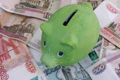 Green piggy bank and russian rubles - stock photo