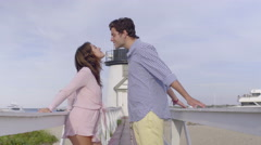 Attractive Couple Lean In For Kiss, Then Walk Hand In Hand Toward Lighthouse Stock Footage