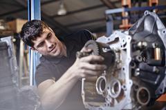 Mechanic fixing part in auto repair shop Stock Photos