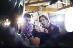 Mechanics examining part in auto repair shop Stock Photos