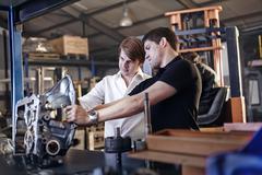 Mechanic and customer examining part in auto repair shop Stock Photos