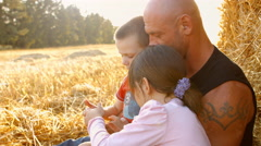 A family of three in a wheat field. Children play on the tablet. 4K 30fps Stock Footage