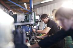 Mechanics using machinery in auto repair shop Stock Photos