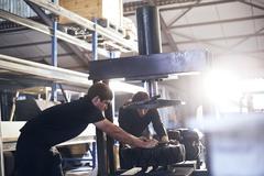 Mechanics fixing tire in auto repair shop Stock Photos