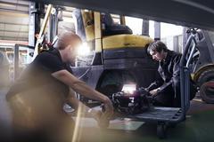 Mechanics fixing forklift in auto repair shop Stock Photos