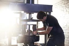 Mechanic using tire changer machine in auto repair shop - stock photo