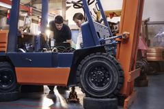Mechanics examining forklift in auto repair shop Stock Photos
