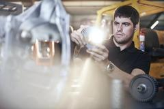 Mechanic examining part in auto repair shop Stock Photos