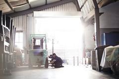 Stock Photo of Mechanics repairing forklift in auto repair shop