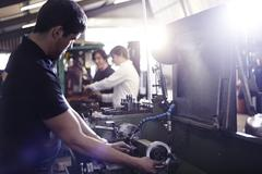 Mechanic working on machinery part in auto repair shop Stock Photos
