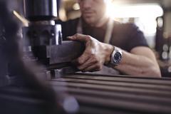 Close up mechanic using machinery in auto repair shop Stock Photos