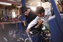 Mechanics working on car in auto repair shop Stock Photos