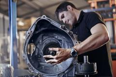 Mechanic fixing part in auto repair shop - stock photo