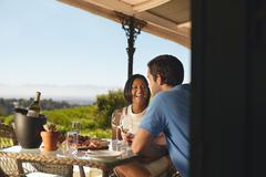 Happy young couple drinking wine at winery - stock photo